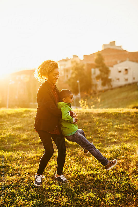Mother and her son playing in the park at sunset. by BONNINSTUDIO for Stocksy United