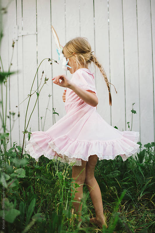 Child spinning in grass with bunny mask on by Kristin Rogers Photography for Stocksy United
