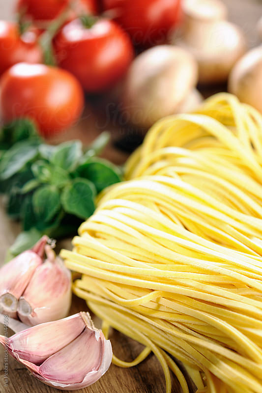 Pasta ingredients, fresh Tagliatelle, garlic, mushrooms, oregano, tomatoes and oregano by Ina Peters for Stocksy United