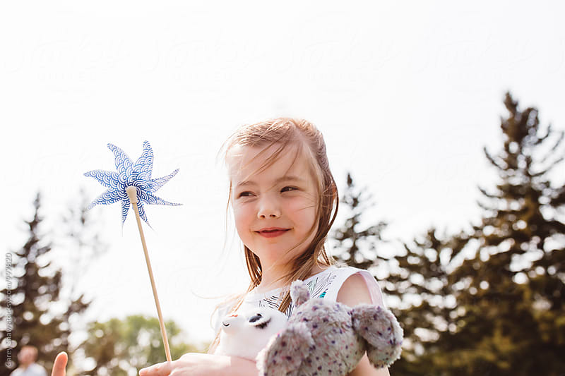 Happy young girl playing with pinwheel outside by Carey Shaw for Stocksy United