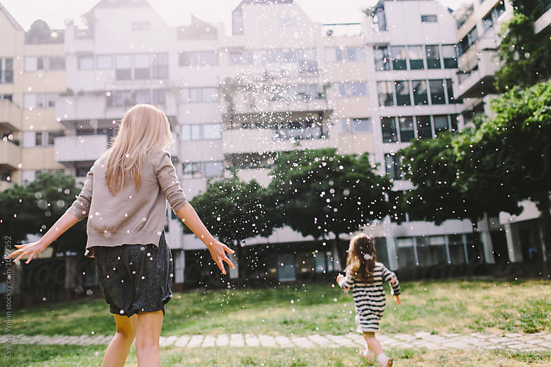 Little girl playing with her mother in sprays of water in town square  by Evgenij Yulkin for Stocksy United