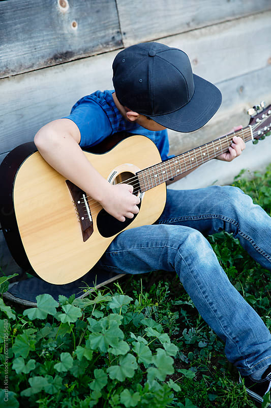 Boy sitting on grass playing his guitar by Curtis Kim for Stocksy United