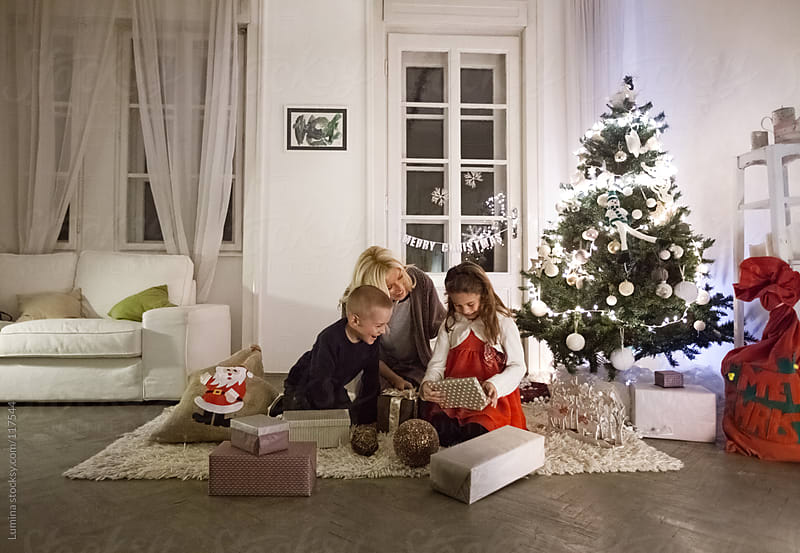 Happy Family Opening Christmas Presents by Lumina for Stocksy United