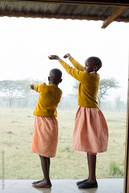 School children having fun during a rain storm. Kenya. by Hugh Sitton for Stocksy United