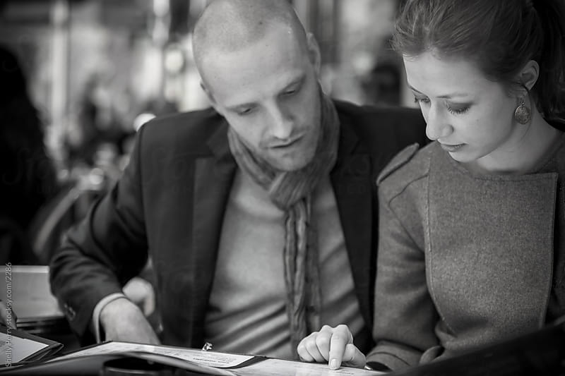 Couple looking over menu in Paris cafe by Shelly Perry for Stocksy United