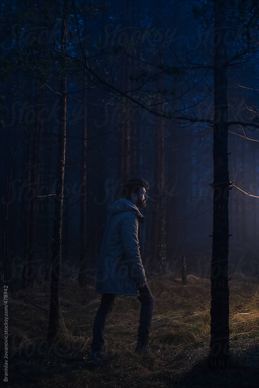Man walking in the forest at night by Brkati Krokodil for Stocksy United