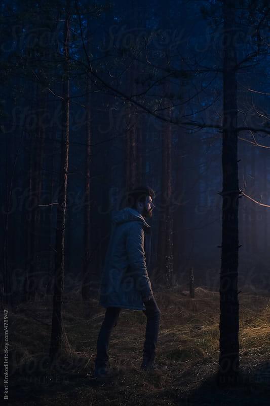 Man walking in the forest at night by Branislav Jovanović for Stocksy United