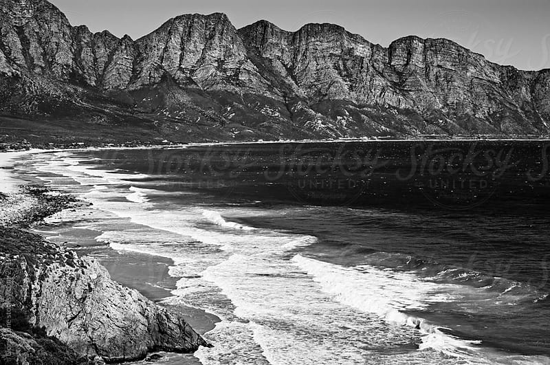 Black and white landscape of a bay by mountain cliffs by Lior + Lone for Stocksy United