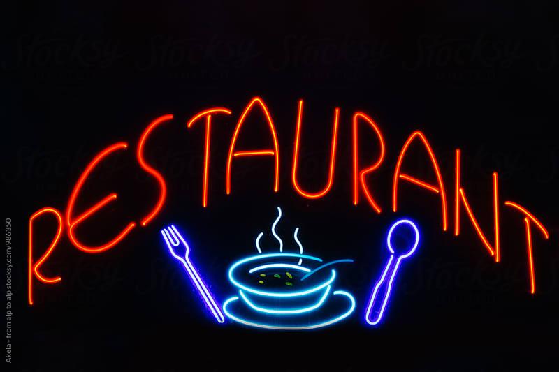 restaurant neon sign on black background  by Leander Nardin for Stocksy United