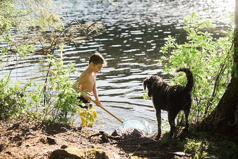 child with dog by a lake by Léa Jones for Stocksy United