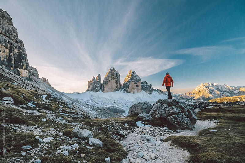 young alpine climber with red jacket looking at the famous three pinnacles at sunrise - italian alps by Leander Nardin for Stocksy United