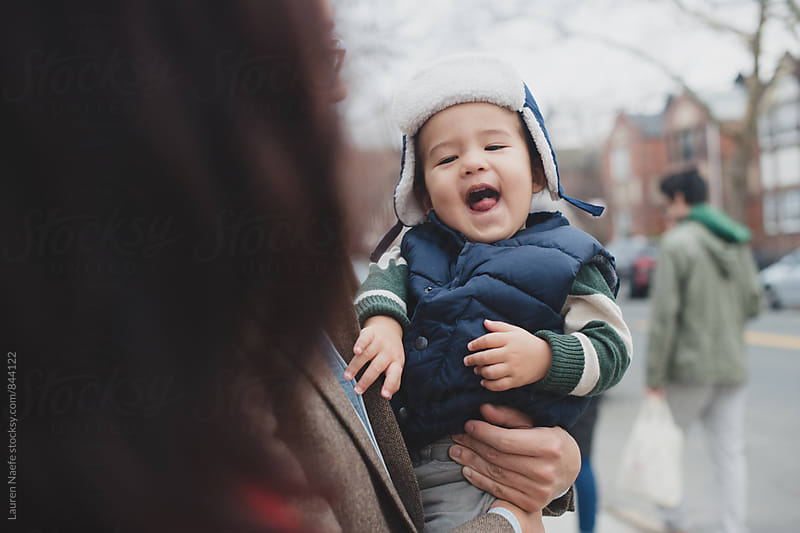 Happy toddler outside in winter cap by Lauren Naefe for Stocksy United