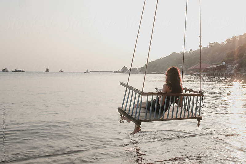 Young girl using tablet computer in seated rope swing over the ocean water on tropical island by Soren Egeberg for Stocksy United