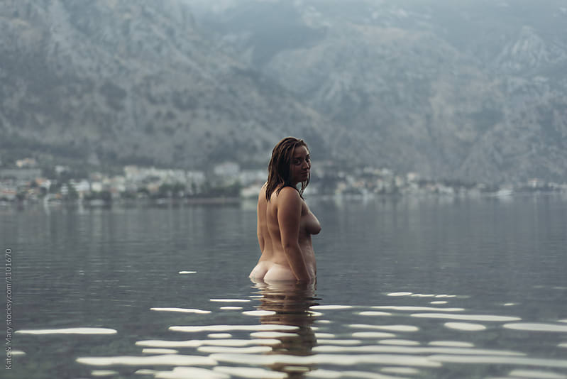 Portrait of naked woman standing in sea by Kate & Mary for Stocksy United