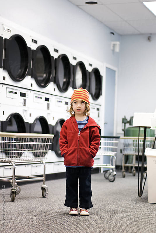 Boy stands alone in laundromat by Cara Dolan for Stocksy United