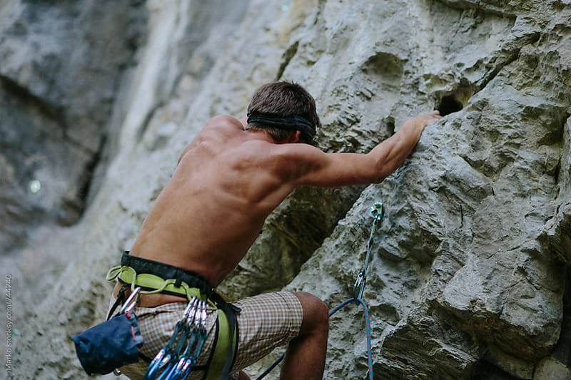 Outdoor couple climbing together at natural rock by Marko Milovanović for Stocksy United