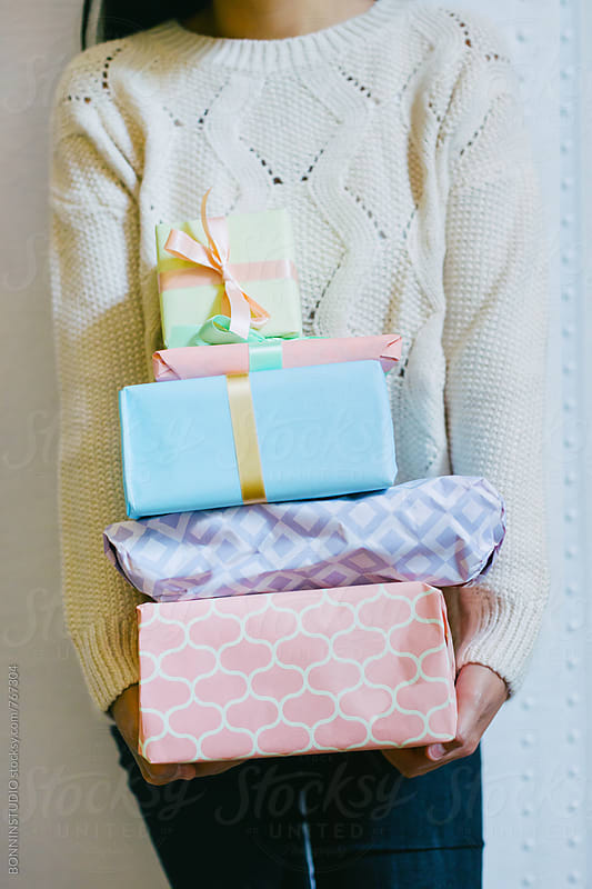 Anonymous woman holding Christmas presents. by BONNINSTUDIO for Stocksy United