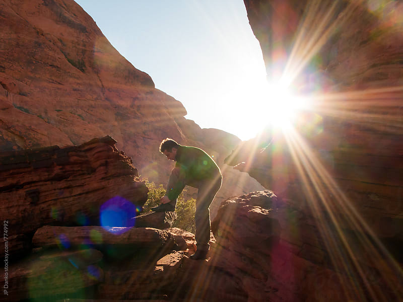 Man Tying Shoes for Rock Climbing Bouldering In Red Rock Canyon Las Vegas Nevada by JP Danko for Stocksy United