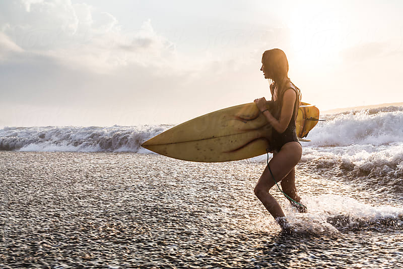 Woman running out of the water with surfboard by Felix Hug for Stocksy United