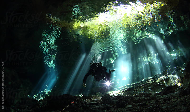 a diver break through a cave by Nat sumanatemeya for Stocksy United