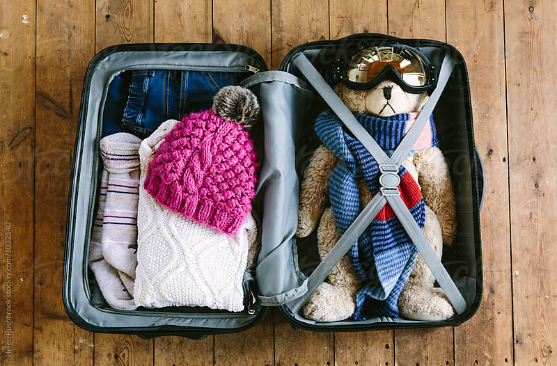 A child's suitcase packed for a winter trip. by Helen Rushbrook for Stocksy United