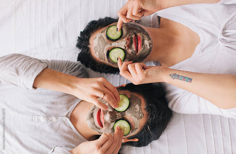 Portrait of two female friends holding facial mask and cucumbers on their faces by Marija Mandic for Stocksy United