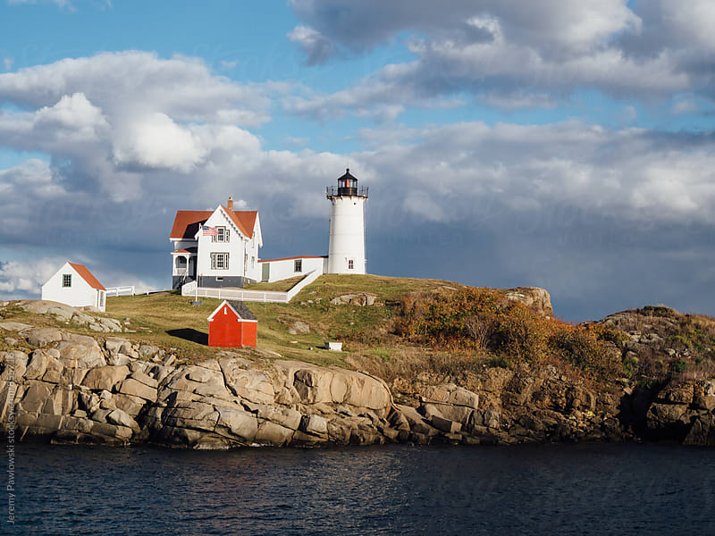 Maine lighthouse on the ocean water. Red and white. by Jeremy Pawlowski for Stocksy United