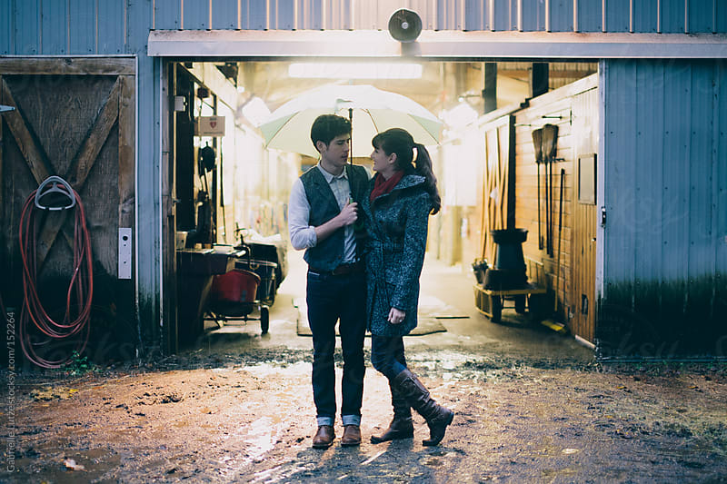 Couple together in the Rain by a Barn by Gabrielle Lutze for Stocksy United
