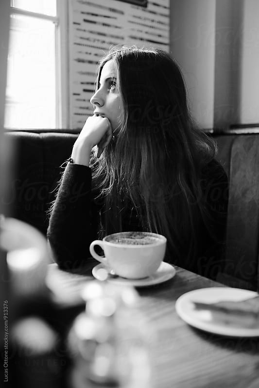 Young woman thinking over a cup of coffee by Lucas Ottone for Stocksy United