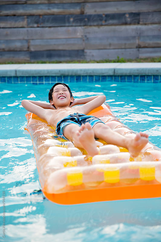Young boy relaxing on inflatable swim float by Curtis Kim for Stocksy United