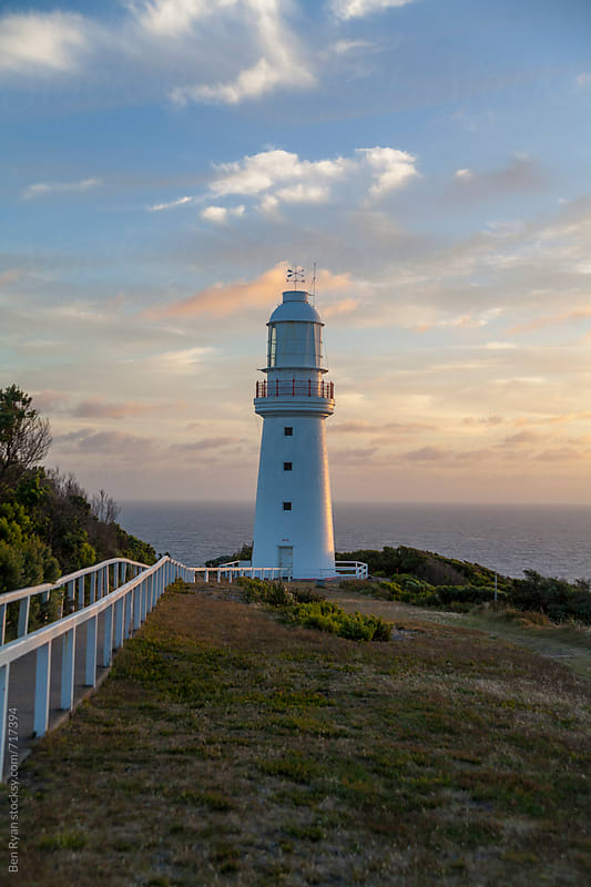 Remote lighthouse with ocean in background at sunset by Ben Ryan for Stocksy United