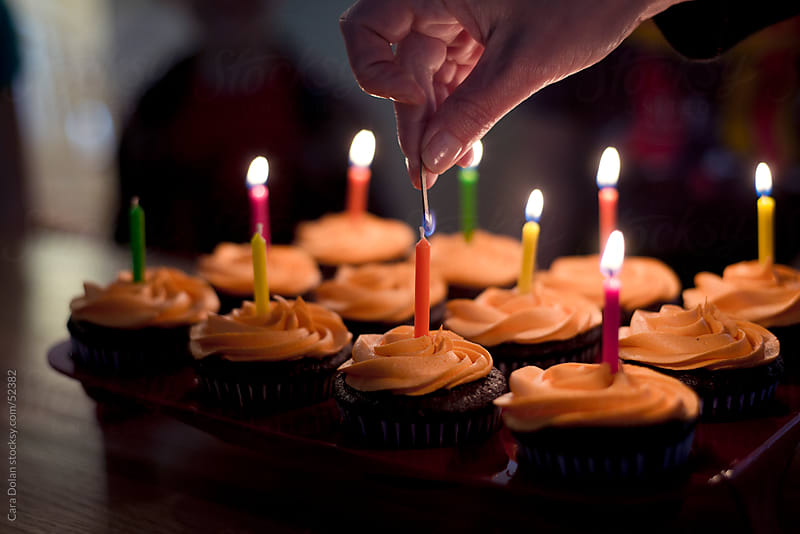 Lighting the candles on birthday cupcakes by Cara Dolan for Stocksy United