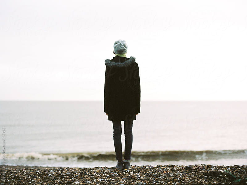 Rear view of teenage girl standing on a beach in England by Kirstin Mckee for Stocksy United