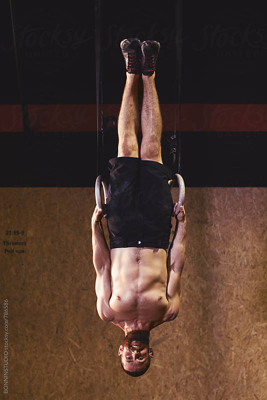 Man doing a handstand with rings in a gym box. by BONNINSTUDIO for Stocksy United