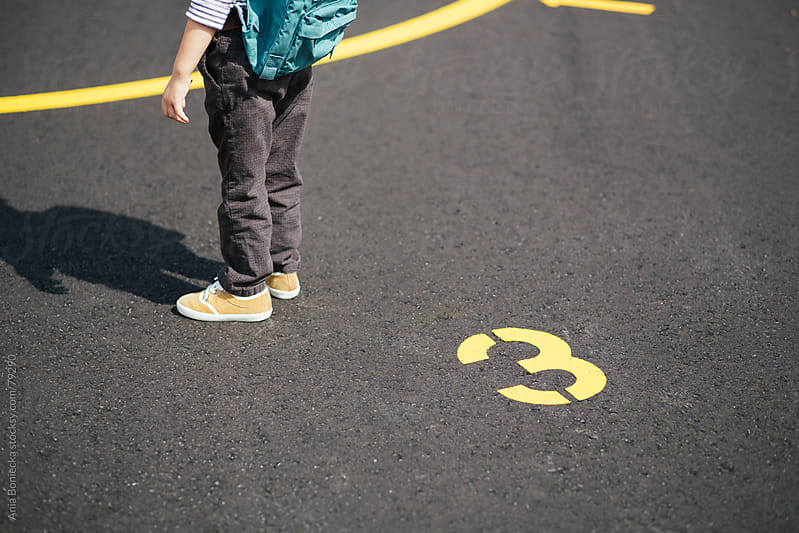 A set of boys legs standing by the number 3 on a cement ground by Ania Boniecka for Stocksy United