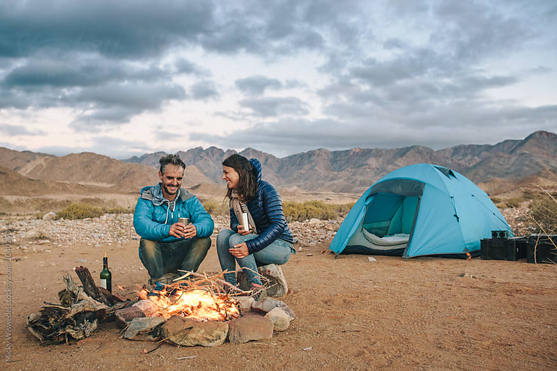 Hiker couple sitting at a camp fire amongst rugged desert mountains by Micky Wiswedel for Stocksy United