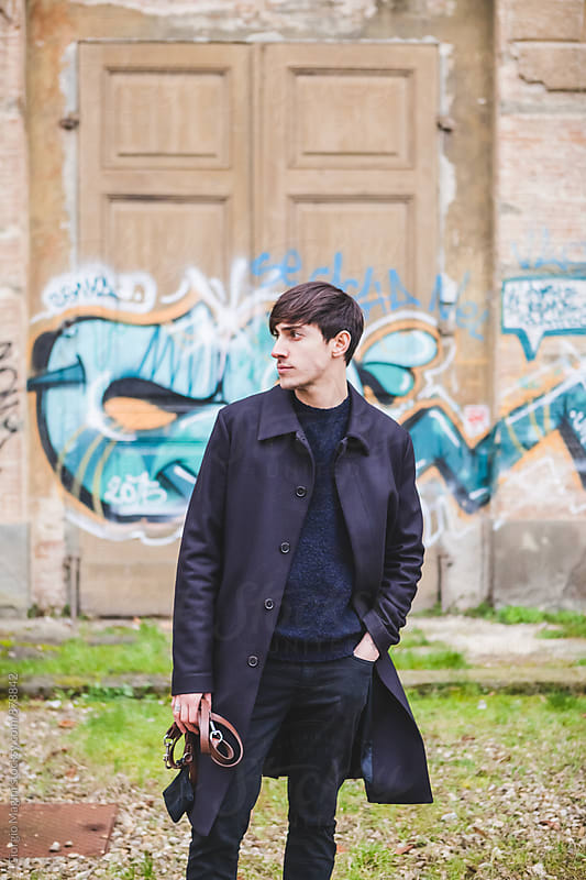 Young Man with Black Coat in Ruined Urban Area by Giorgio Magini for Stocksy United