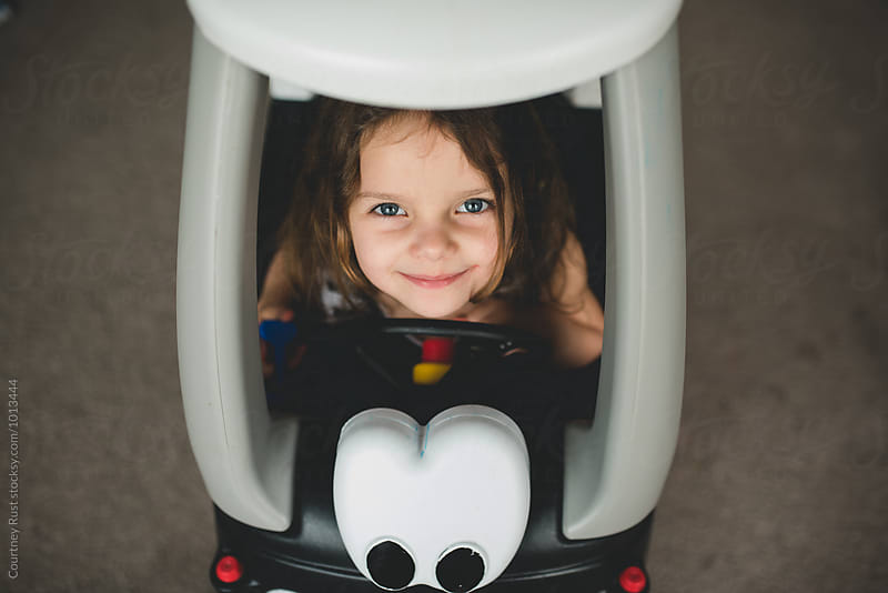 Funny faces driving toy car by Courtney Rust for Stocksy United