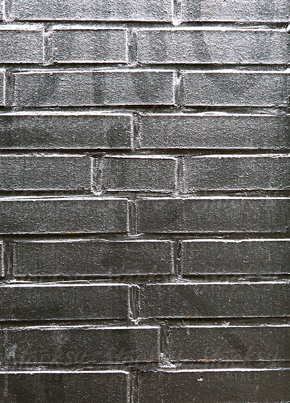 brick wall painted shiny silver by Marcel for Stocksy United