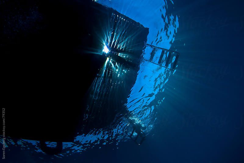 Underwater ocean view looking up at dive boat with sun rays shining through by Soren Egeberg for Stocksy United