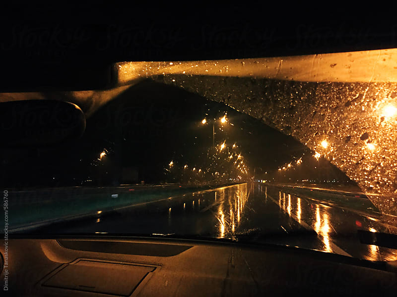 View on the empty wet road from the car by Dimitrije Tanaskovic for Stocksy United
