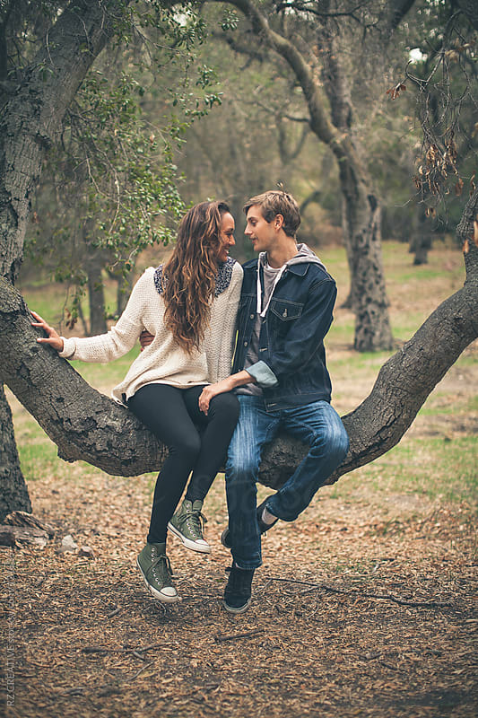 Portrait of attractive young couple sitting in a tree. by RZ CREATIVE for Stocksy United