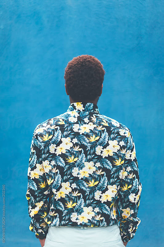 Back view of modern young black man with sunglasses in front blue background. by BONNINSTUDIO for Stocksy United