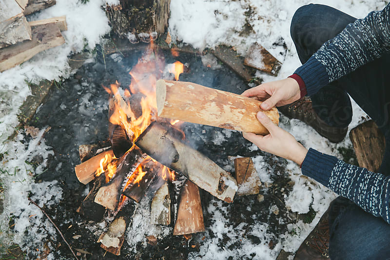 Hands addig wood to a bonfire outdoors in the snow by Lior + Lone for Stocksy United