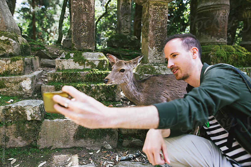 Man taking a selfie with a young deer in the woods.  by BONNINSTUDIO for Stocksy United