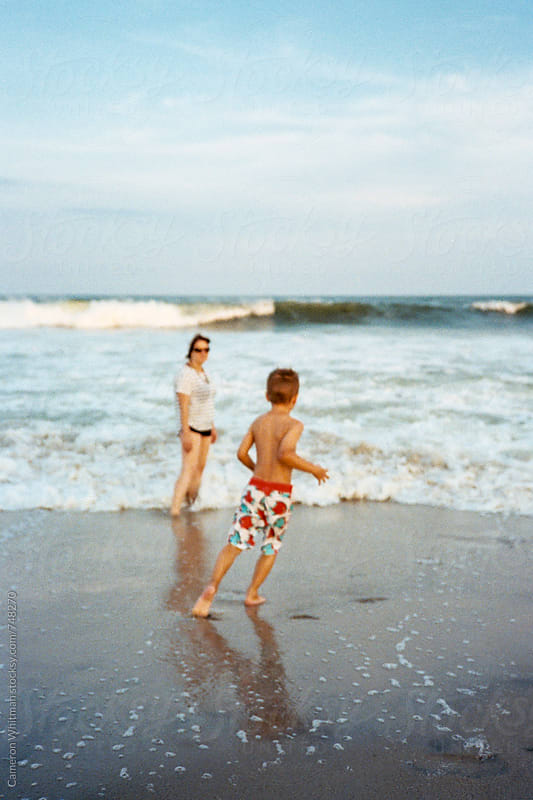 Mother and Son playing on the beach at sunset  by Cameron Whitman for Stocksy United