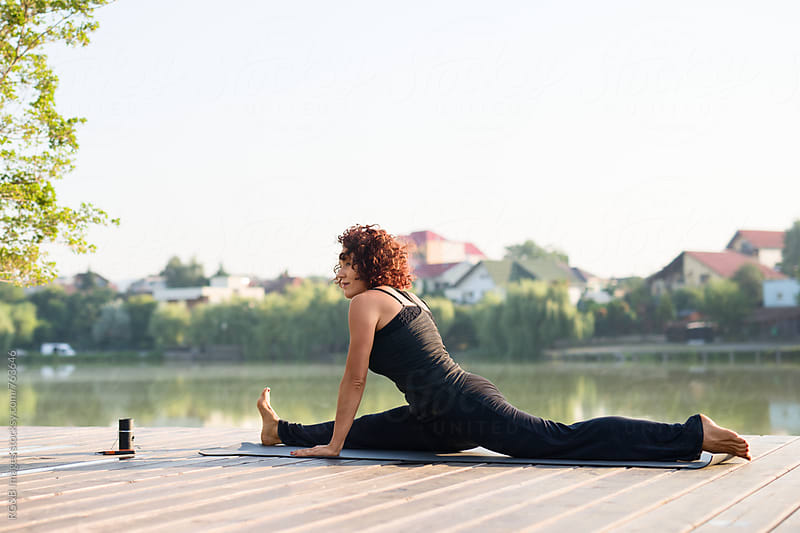 Woman doing yoga or pillates stretching outdoor by RG&B Images for Stocksy United