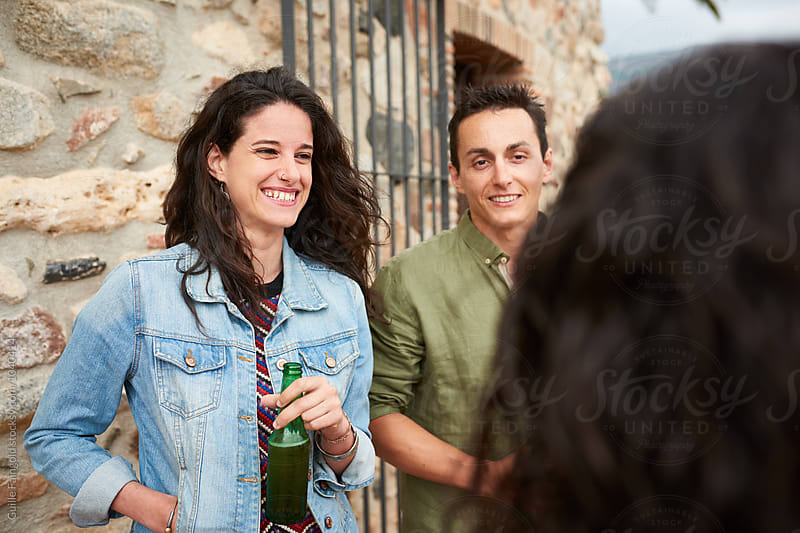 Young couple smiling while having party in garden by Guille Faingold for Stocksy United