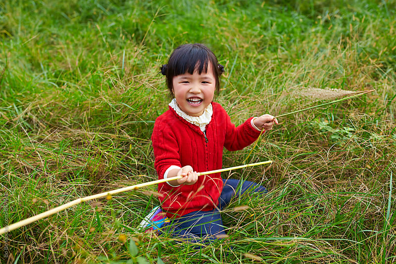 one happy little asian girl outdoor in the grassland by cuiyan Liu for Stocksy United