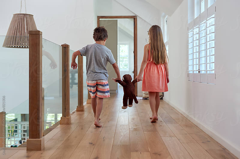 Boy and girl holding hands of plush teddy bear walking inside house 